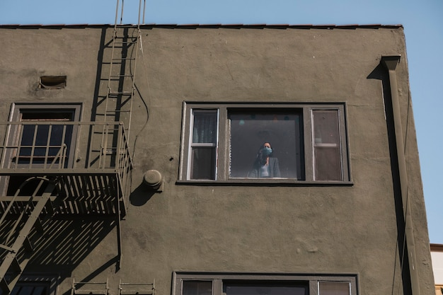Donna che guarda fuori dalla finestra del suo appartamento nel centro di los angeles durante la pandemia di covid-19