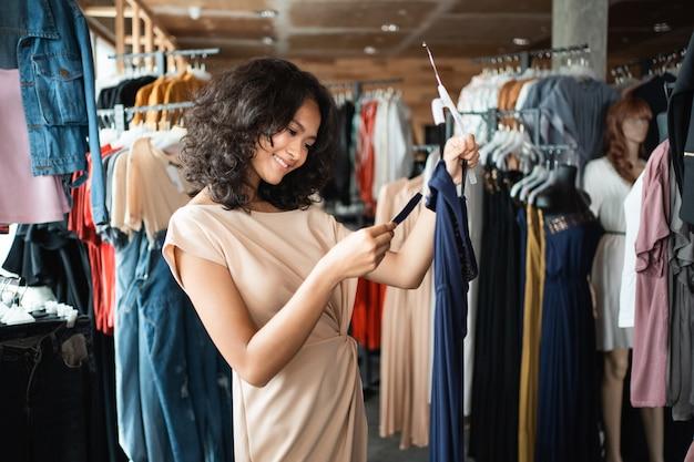 Donna che esamina un prezzo da pagare mentre vestito da compera