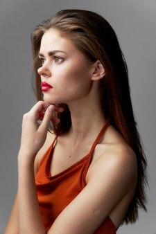 Donna che guarda al lato vestito arancione vista ritagliata del modello di rossetto di lusso