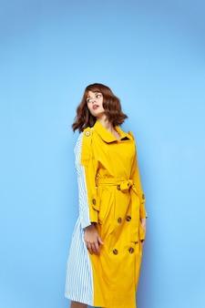Donna che guarda al lato e cappotto giallo con bottoni vestiti alla moda in tessuto a righe