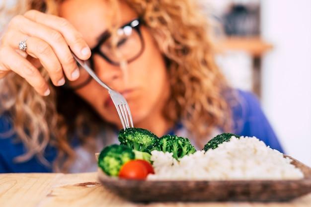 Donna che guarda con disgusto alcune verdure e si alza sul tavolo - non mangerà questo perché preferisce una cattiva alimentazione - cercando di perdere peso