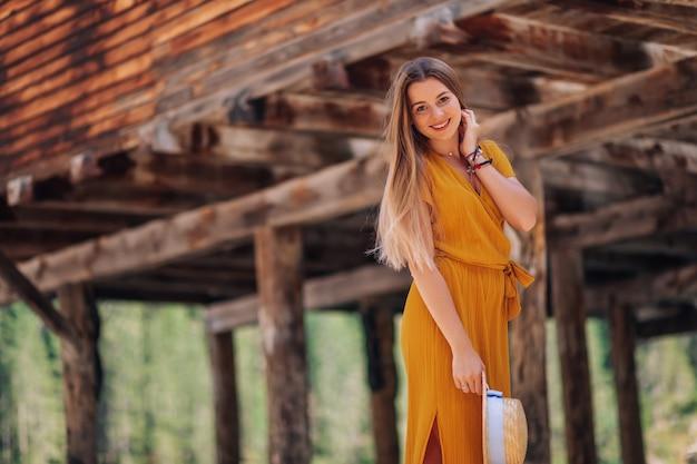 La donna guarda la telecamera e sorride vicino a un edificio in legno
