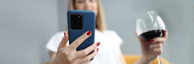 La donna guarda nello smartphone e tiene in mano un bicchiere di vino