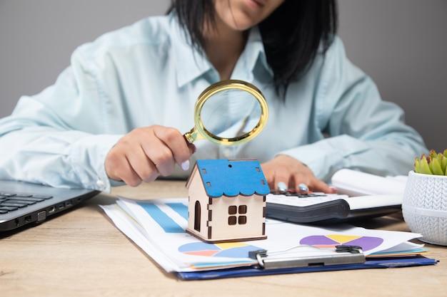 La donna guarda il modello di casa con una lente d'ingrandimento