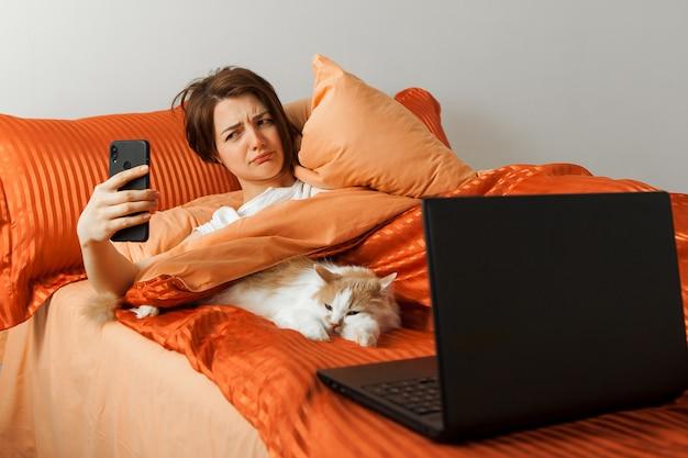 La donna guarda lo schermo del telefono scontento, sveglia sdraiata a letto. sul letto accanto c'è un computer portatile e un gatto dorme