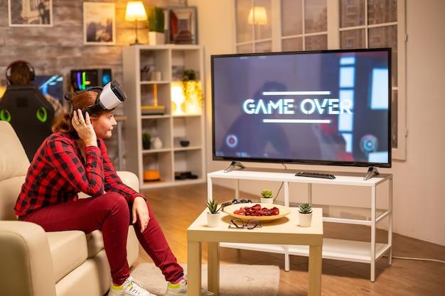 Donna che perde ai videogiochi mentre gioca con l'auricolare per realtà virtuale a tarda notte nel soggiorno