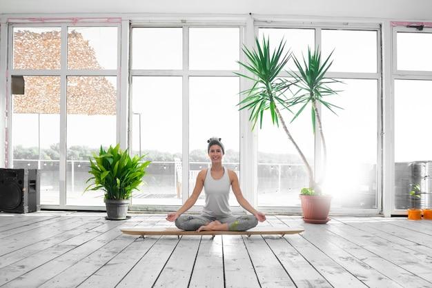 Donna nella posizione del loto sulla tavola sup indoor durante la sua lezione di yoga mattutina.