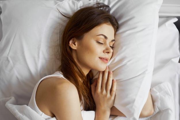 Donna sdraiata sul letto comodo cuscino riposo mattutino