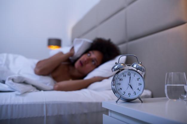 Donna sdraiata a letto affetta da insonnia, donna insonne e disperata sveglia di notte non in grado di dormire, sentirsi frustrata e preoccupata soffrendo di insonnia nel disturbo del sonno