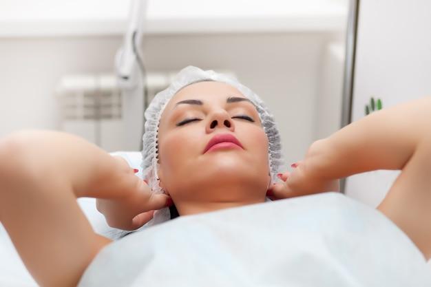 Donna sdraiata sul letto mentre riceve l'iniezione di bellezza nel collo. trattamenti viso. concetto di bellezza.