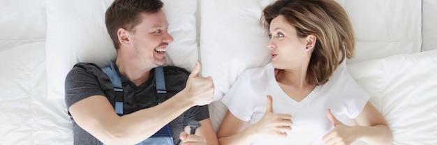 Donna sdraiata a letto con l'amante dell'idraulico e che mostra pollice in alto vista dall'alto. marito per un'ora concetto