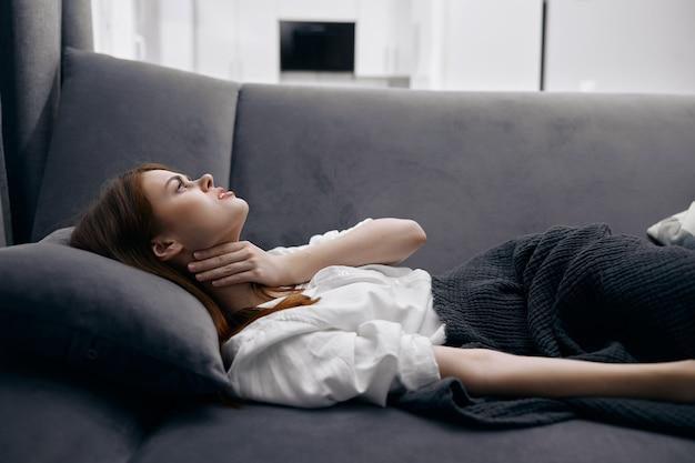 Donna sdraiata sul divano mano sul collo sensazione di malessere problemi di salute