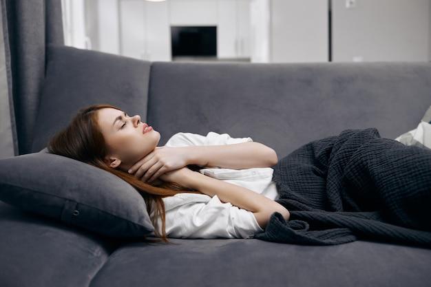 Donna sdraiata sul divano a casa tenendo i suoi problemi di salute del collo