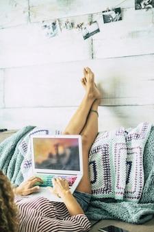 La donna sdraiata sul divano con le gambe appoggiate al muro si rilassa guardando il computer. guardare film in streaming o lavorare in un ufficio alternativo e in una posizione del corpo. donne a casa con la tecnologia