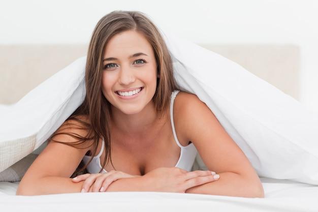 Donna sdraiata alla fine del letto, sorridendo mentre guarda avanti