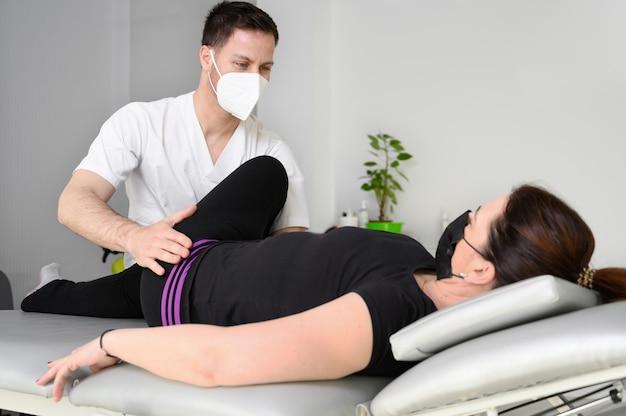 Donna sdraiata sul lettino da massaggio mentre il suo fisioterapista fa esercizi speciali per la terapia fisica per la sciatica e problemi ai nervi pizzicati.