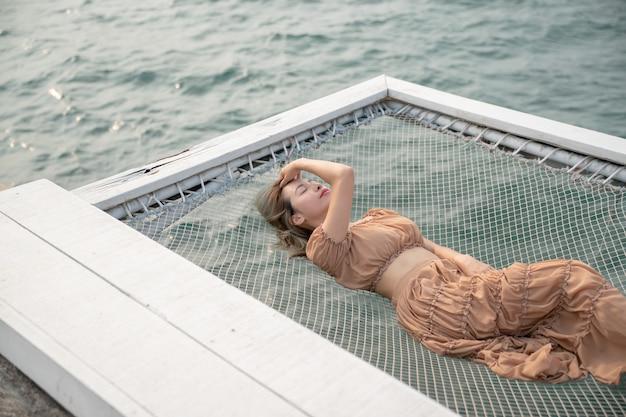 Donna sdraiata su un molo con sfondo mare, seduta in rete in riva al mare.