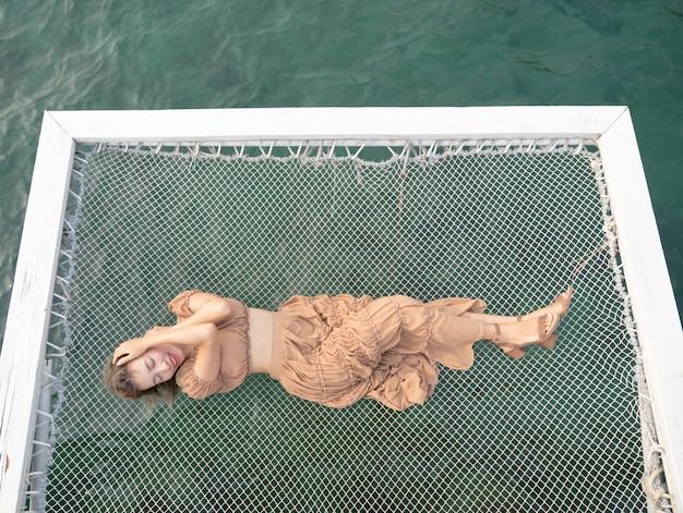 Donna sdraiata su un molo con il mare, seduta sulla rete in riva al mare.