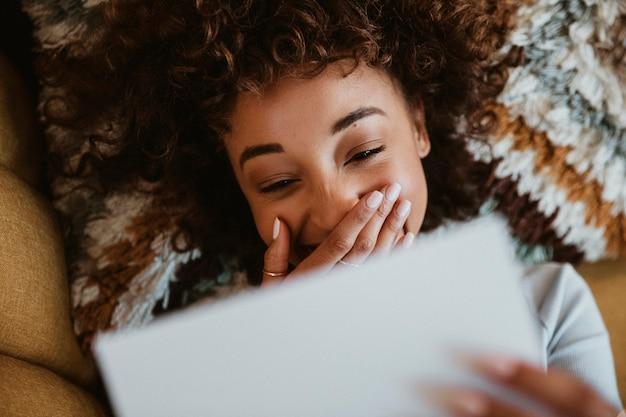 Donna sdraiata e leggendo una lettera su un divano