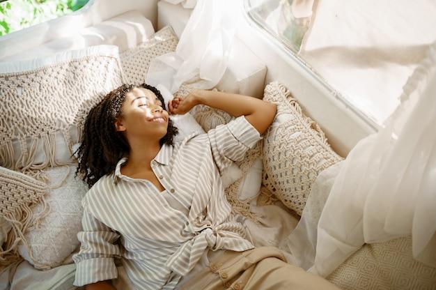 Donna sdraiata nel letto del camper, vista dall'alto, campeggio in un rimorchio. coppia viaggia in furgone, vacanze in camper, svaghi in camper in camper