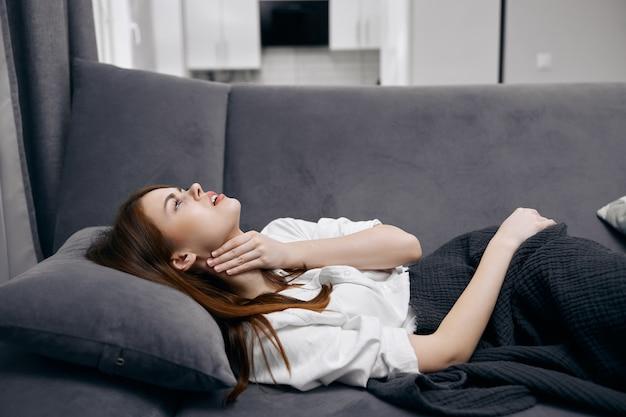 Donna sdraiata sul divano tenendo i suoi problemi di salute del collo a casa