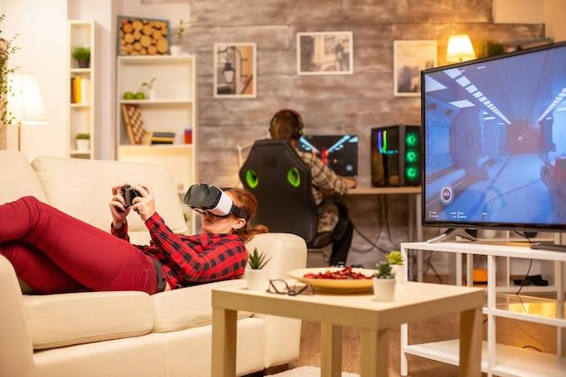 Donna sdraiata sul divano a tarda notte in soggiorno a giocare ai videogiochi utilizzando un auricolare per realtà virtuale