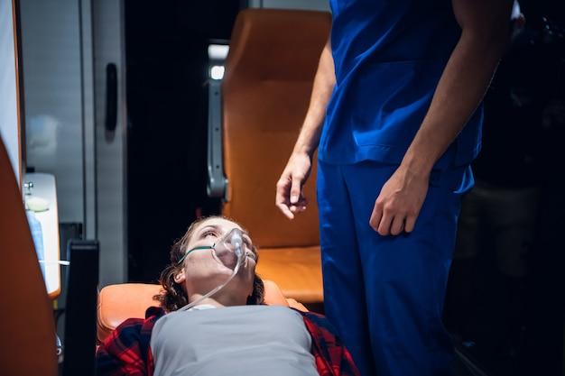 Una donna sdraiata su una barella con una maschera all'ossigeno e guarda il paramedico in uniforme blu.