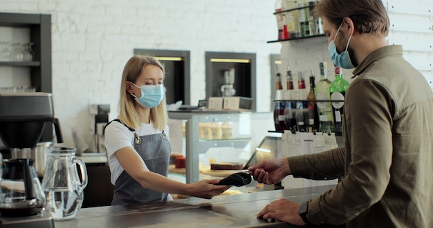 Donna in maschera madica nel proprietario di un bar imprenditore che prepara il caffè per un cliente in un bar