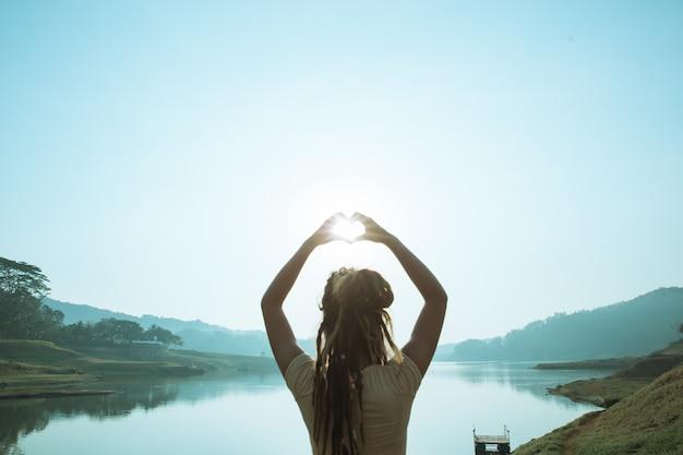 La donna fa una forma di cuore al mattino