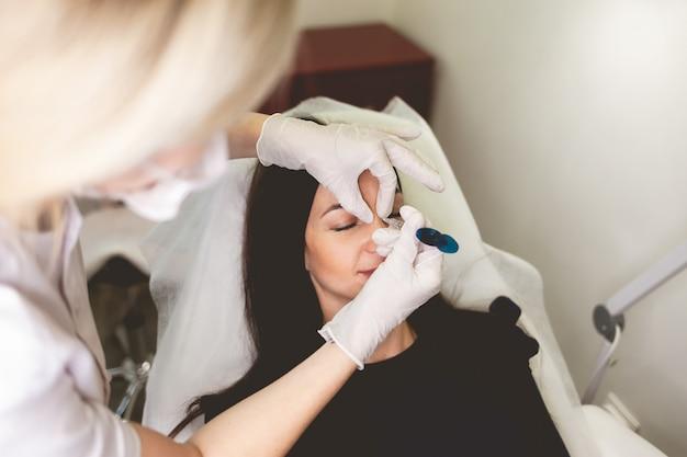 La donna fa l'iniezione di bellezza nel naso.