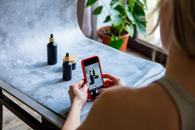 La donna fa una foto del prodotto per la vendita online in internet da casa