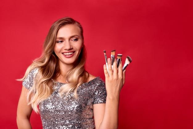 La donna make up artist tenere pennelli cosmetici nelle mani