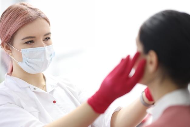 Truccatrice donna in maschera protettiva rende la procedura al cliente nel salone di bellezza. concetto di servizi del salone di bellezza