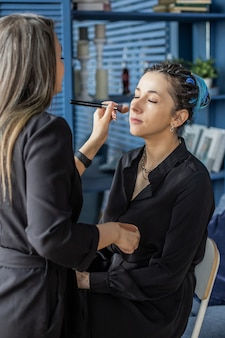 Donna make up master applicando il tono della pelle fondotinta in polvere fard sul viso usa il pennello al salone di bellezza