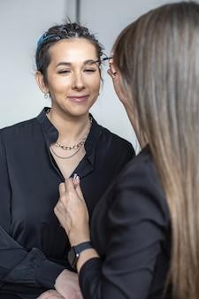 La donna compone il maestro che applica il rossore della polvere del fondotinta della pelle sul viso usa la spazzola al salone di bellezza