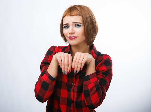 La donna fa il segno di insaccamento con le mani. ritratti di giovane donna con diverse emozioni felici. camicia a scacchi e capelli rossi. emozioni pietose.