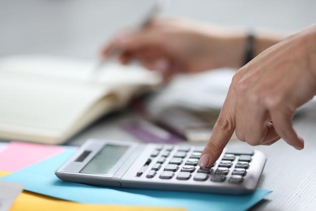 La donna fa i calcoli sulla calcolatrice. concetto di servizio della società di servizi di contabilità