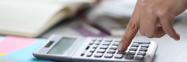 La donna fa i calcoli sulla calcolatrice. concetto di servizio dell'azienda di servizi di contabilità