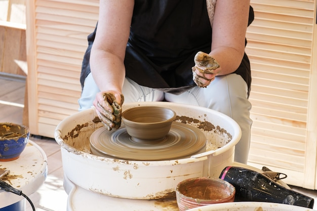 La donna fa piatti di argilla sul tornio da vasaio