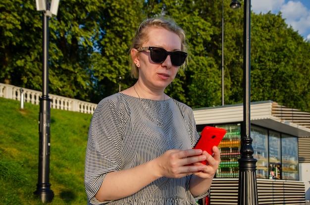 Una donna fa acquisti online o comunica tramite messaggistica istantanea dal suo smartphone mentre è seduta in un parco in una giornata estiva