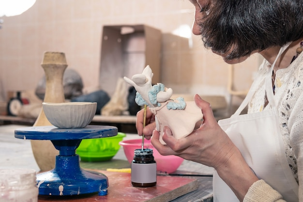 Una donna realizza e dipinge un giocattolo in ceramica fatto di argilla nel laboratorio dello studio.