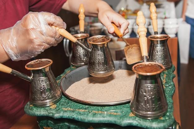 La donna fa il caffè turco su una macchina da caffè con sabbia in cezve. orientale, caffè orientale.