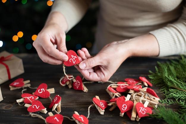 Donna che fa un calendario dell'avvento per il suo bambino, preparazione per il natale, artigianato natalizio fai-da-te.