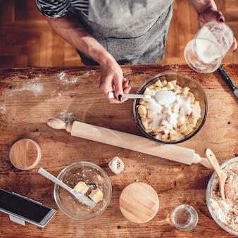Donna che produce la torta di mele sulla tavola di legno