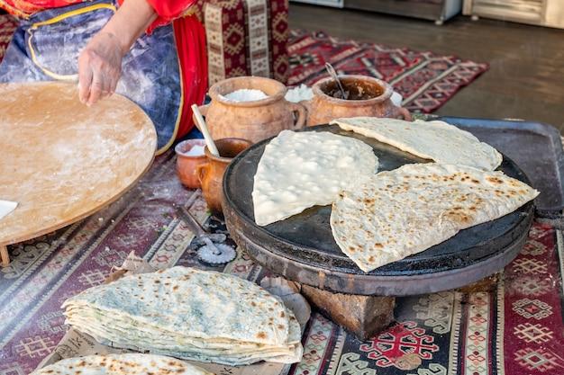 Donna che fa il qutab dell'azerbaigian con i verdi