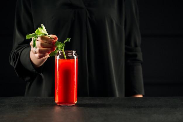 Donna che fa bloody mary cocktail con sedano