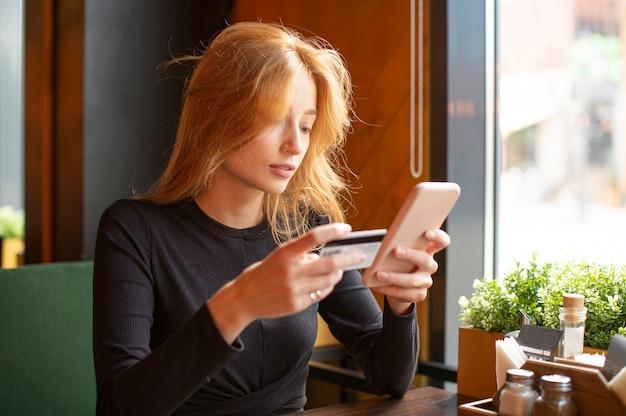 Donna che effettua il pagamento con carta tramite telefono cellulare per pagare le bollette in un bar