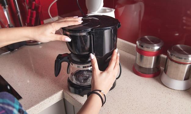 Donna che fa il caffè in una macchina per il caffè.