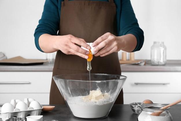 Donna che fa la pasta per i biscotti al burro in cucina