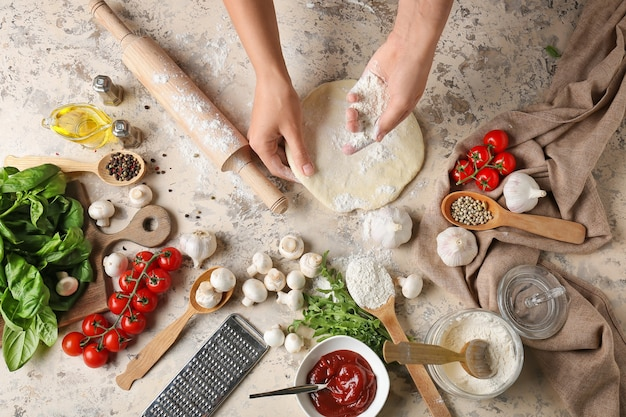 Donna che fa la pasta per pizza sulla superficie chiara